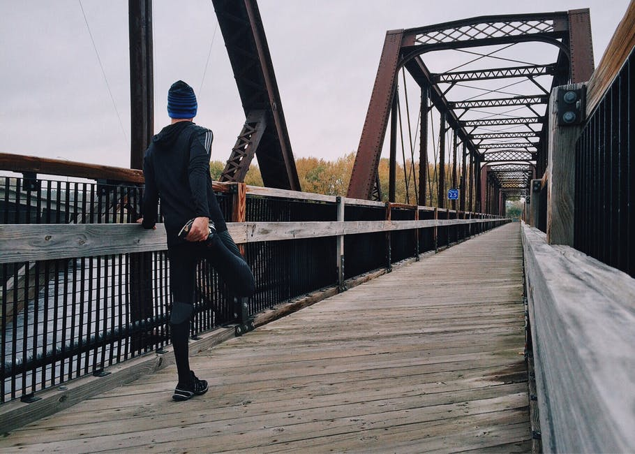 A man sitting on a bench near a bridge